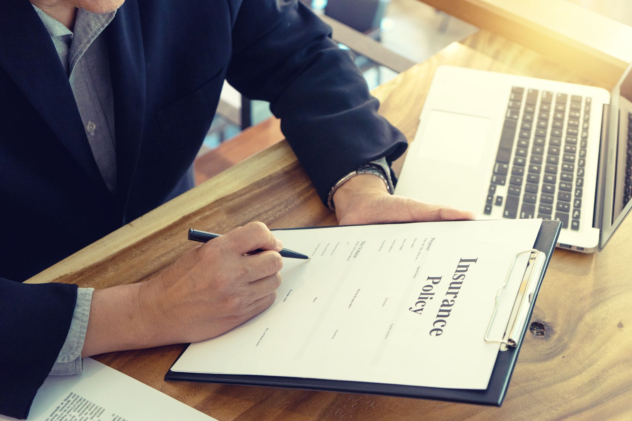 Cropped image of a businessman signing insurance documents