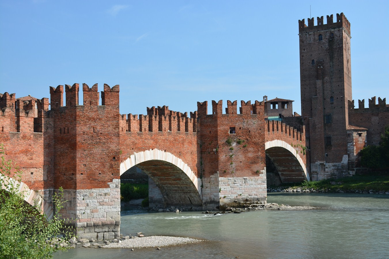 ponte di castelvecchio red stone bridge over adige river on a clear sunny day in verona italy. See it on an Italy road trip