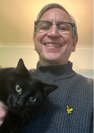 AB instructor Tony smiling and holding a black cat called Barbie
