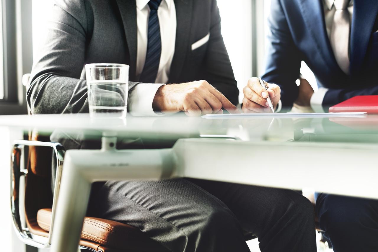 Funcionários em uma mesa discutindo com seus computadores a política do reembolso corporativo