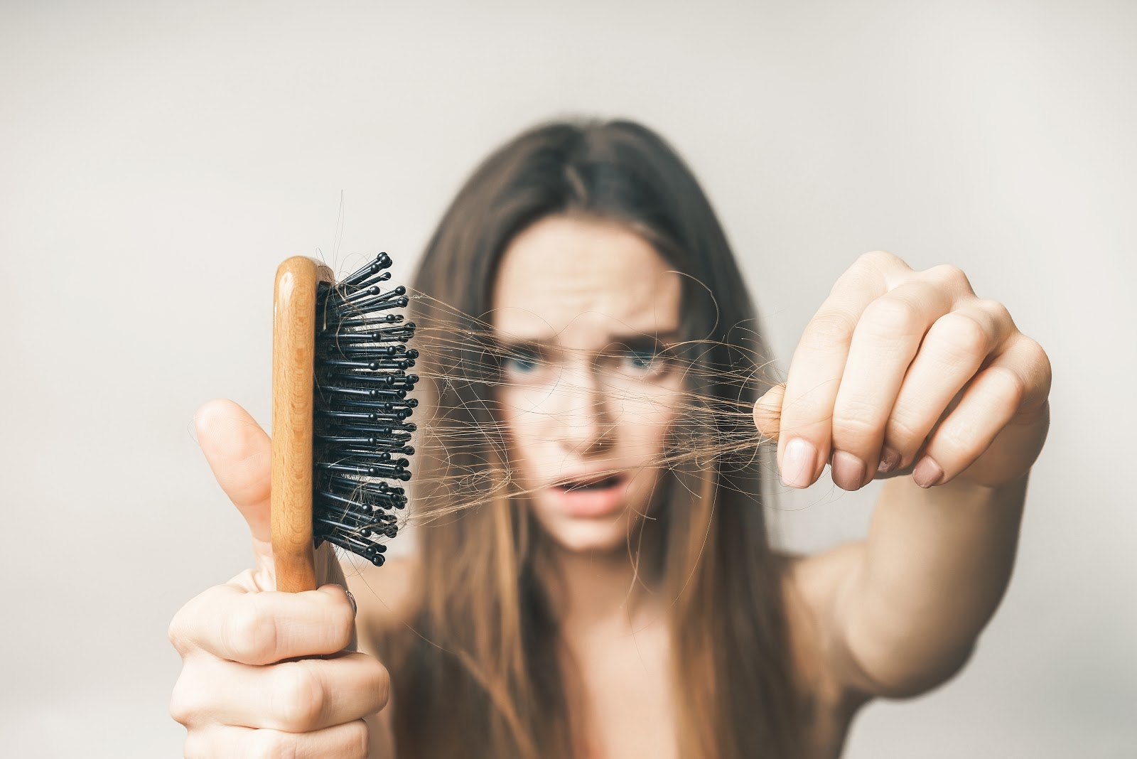 A woman looking at the hair in her hairbrush with concern
