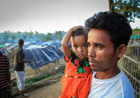 """Myanmar refugees in Bangladesh. Hossain holds Yasminara, his 1 ½-year old daughter, in a Bangladesh refugee camp. """"When it rains we all get wet,"""" he says. (©2018 World Vision/photo by Shabir Hussain)"""