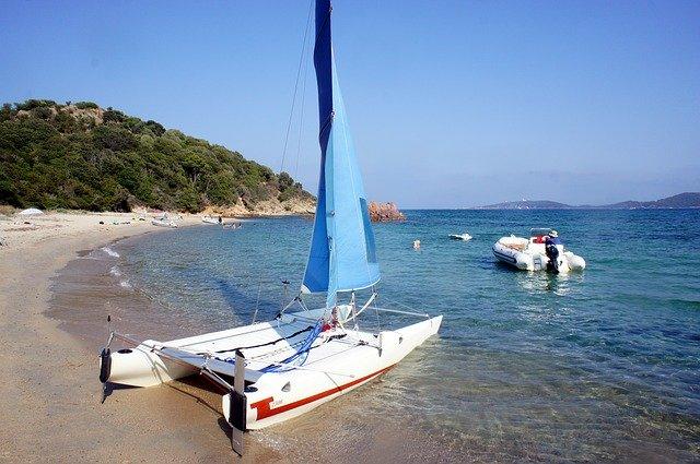 A small sailing catamaran sits on a beach.