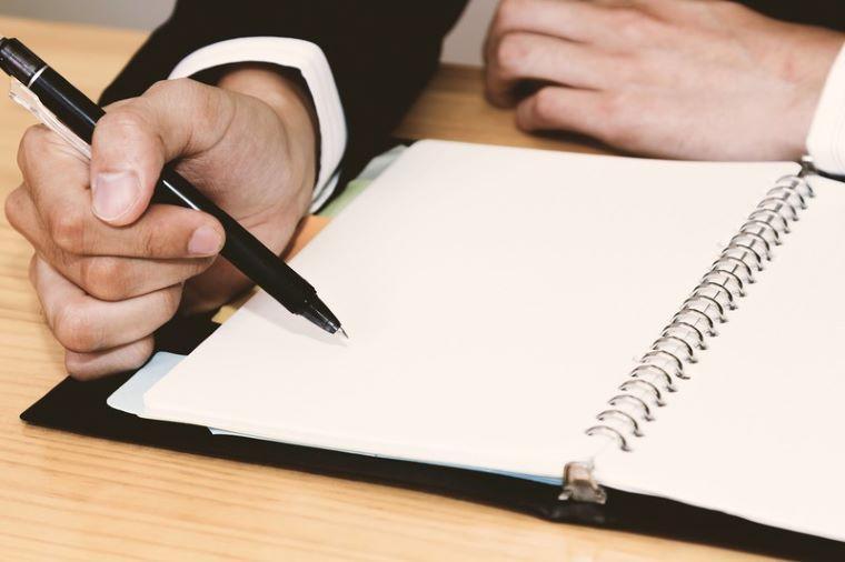 ノートに記入する男性