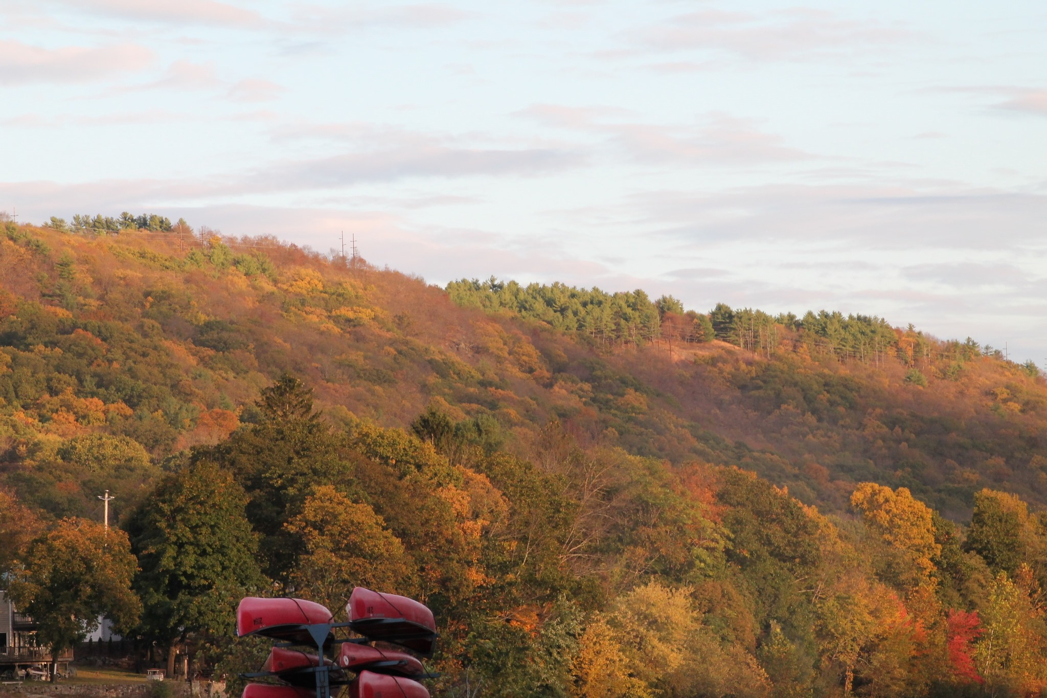 Kayaks piled up next to large hill with fall colors at campground