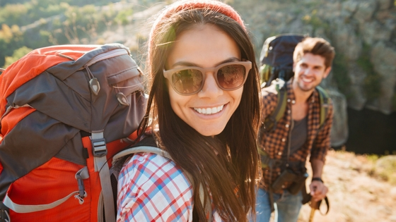 smiling woman wearing sunglasses and a hiking backpack outdoors