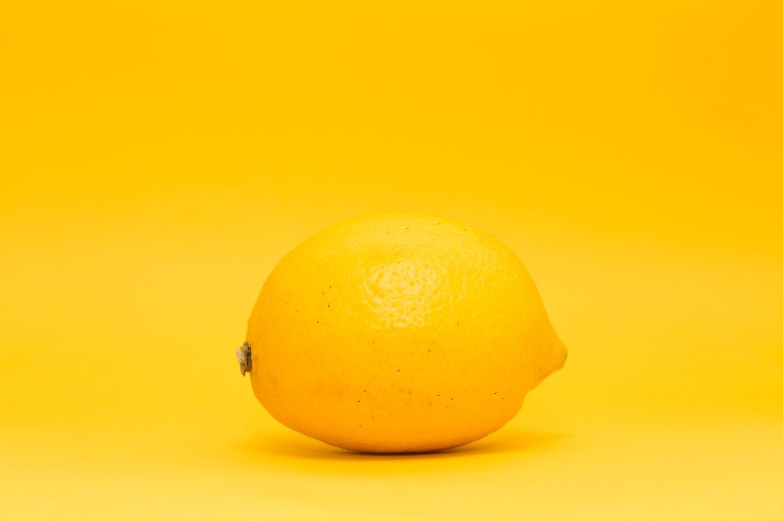 Yellow lemon on a yellow monochrome backdrop