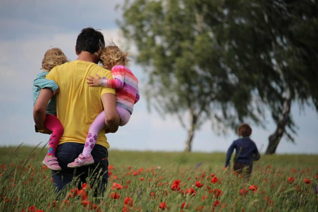 Dad holding twin girls, walking in a field, behind his son who is running ahead. None appear to have body image problems.