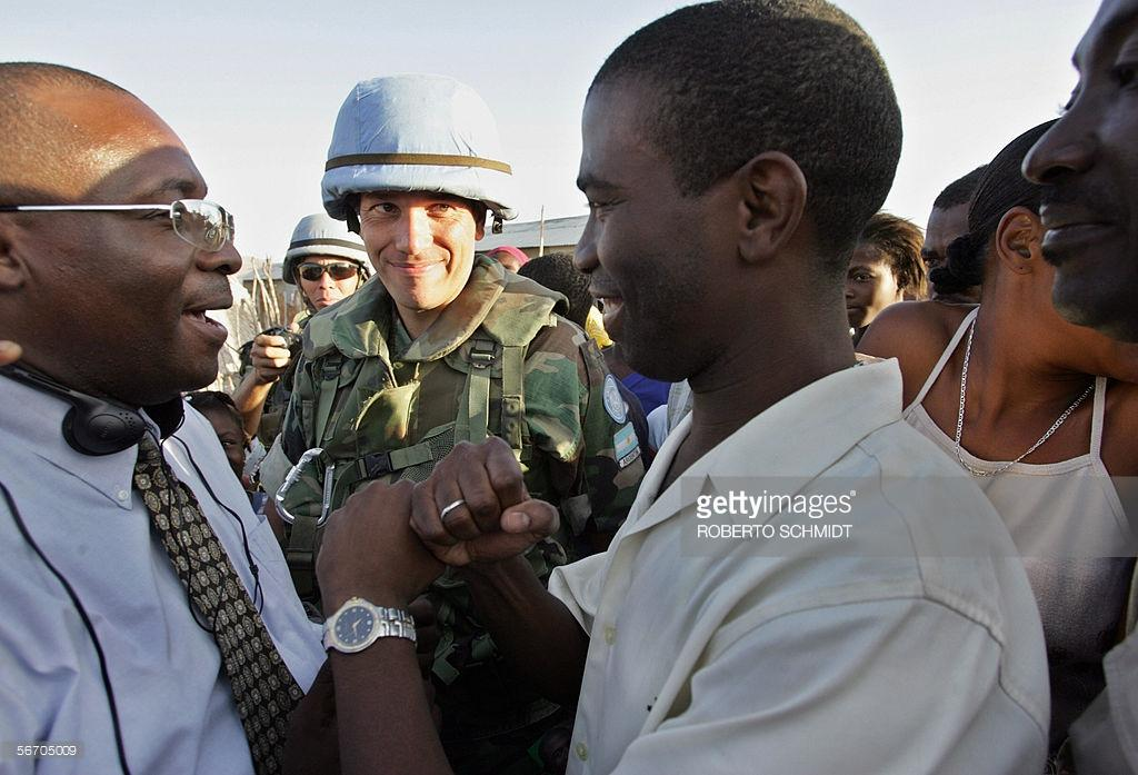 Former rebel commander and presidential candidate Guy Philippe (R) and senatorial candidate Winter Etiene (L) stop to thank Argentinian peacekeepers for their work during a campaign stop in the Raboteau neighborhood of Gonaives 29 January 2006. Philippe, who is now running for president in Haiti's 07 February 2006 elections, took up arms in Gonaives in 2004. The armed rebel movement which took control of the northern part of the country contributed to the departure of then Haitian president Jean Bertrand Aristide. AFP PHOTO/Roberto SCHMIDT