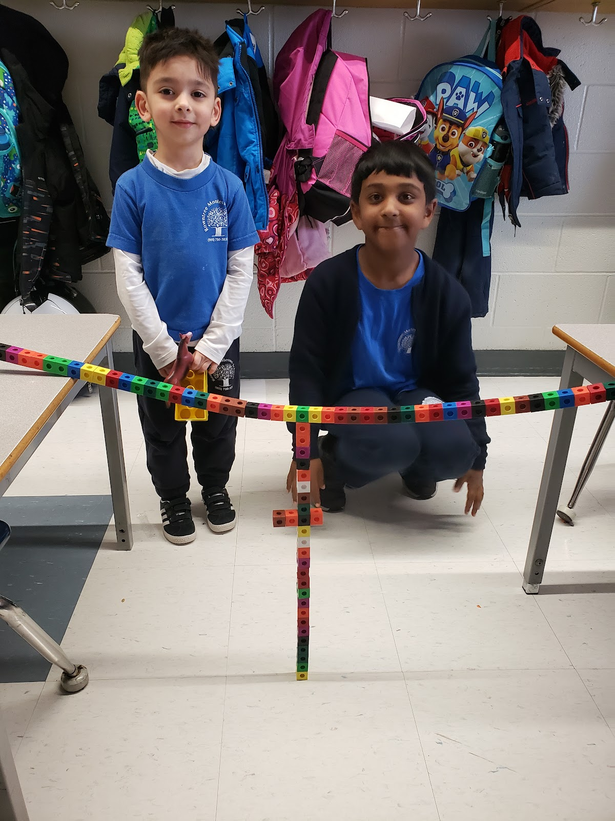 Kindergarten and Grade 1 student at Rowntree Montessori Schools collaboarating on a STEM project bridge.