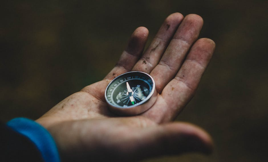 Hand holding a compass; planning for outdoor travel