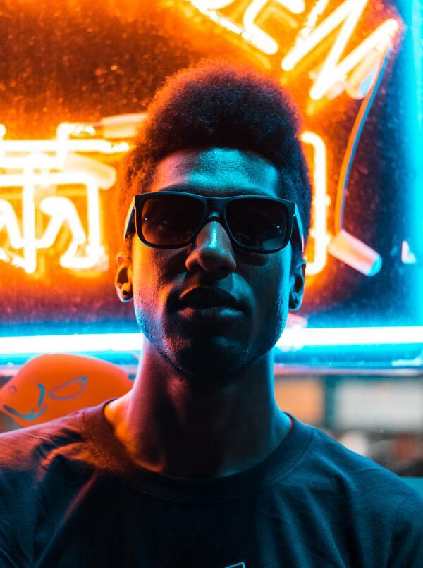 foto de um homem negro em frente a um letreiro colorido de laranja e azul