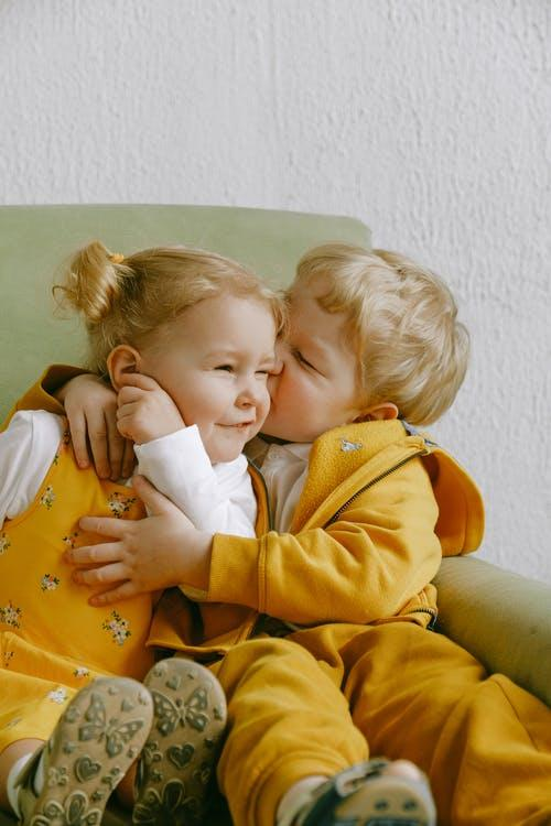 Cheerful little siblings hugging in armchair at home