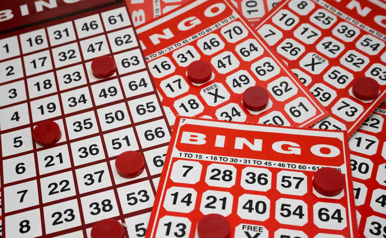 Multiple bingo cards with red counters scattered over them