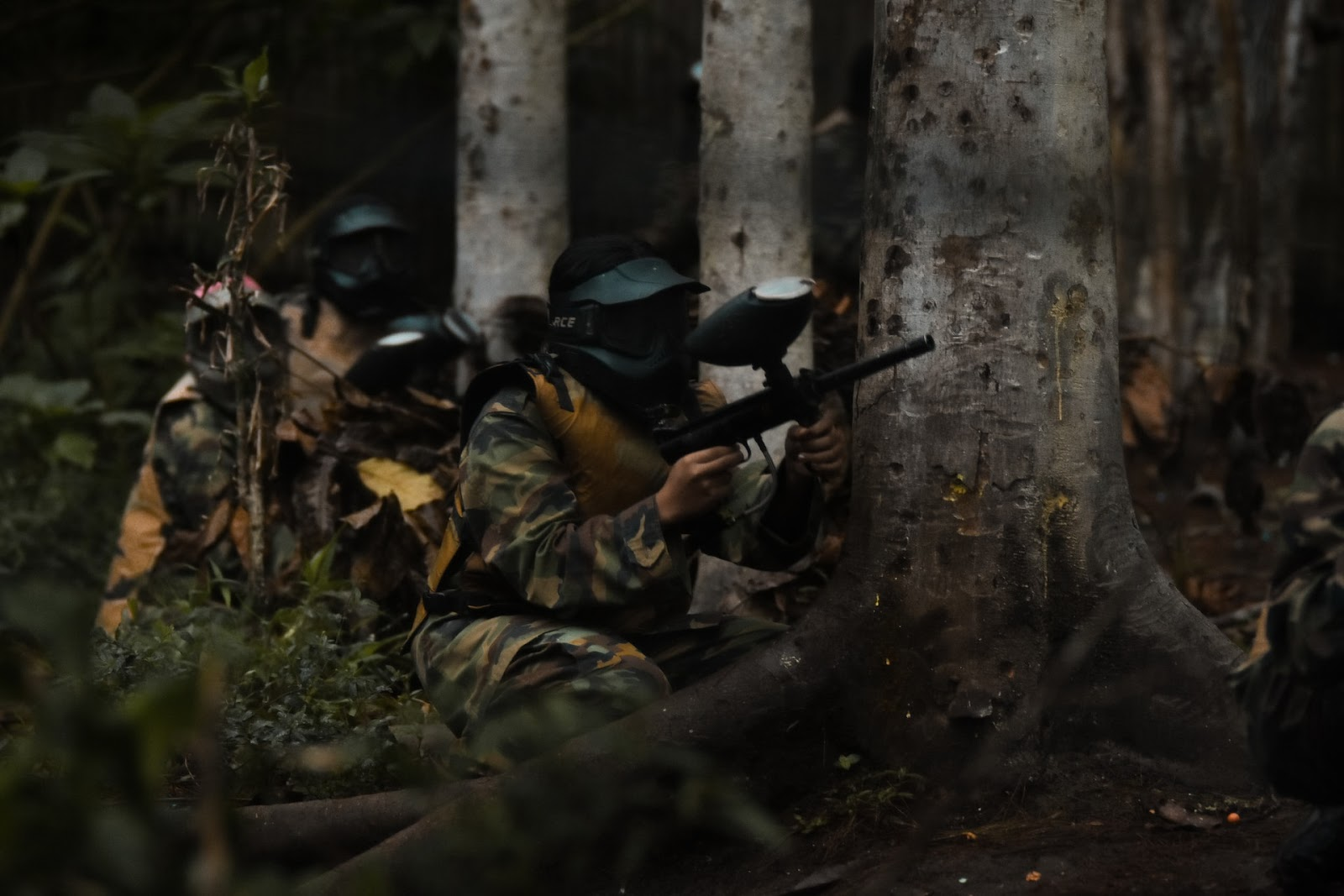 activities for people of all ages, a group of friends hiding behind a tree while playing a match of paintball