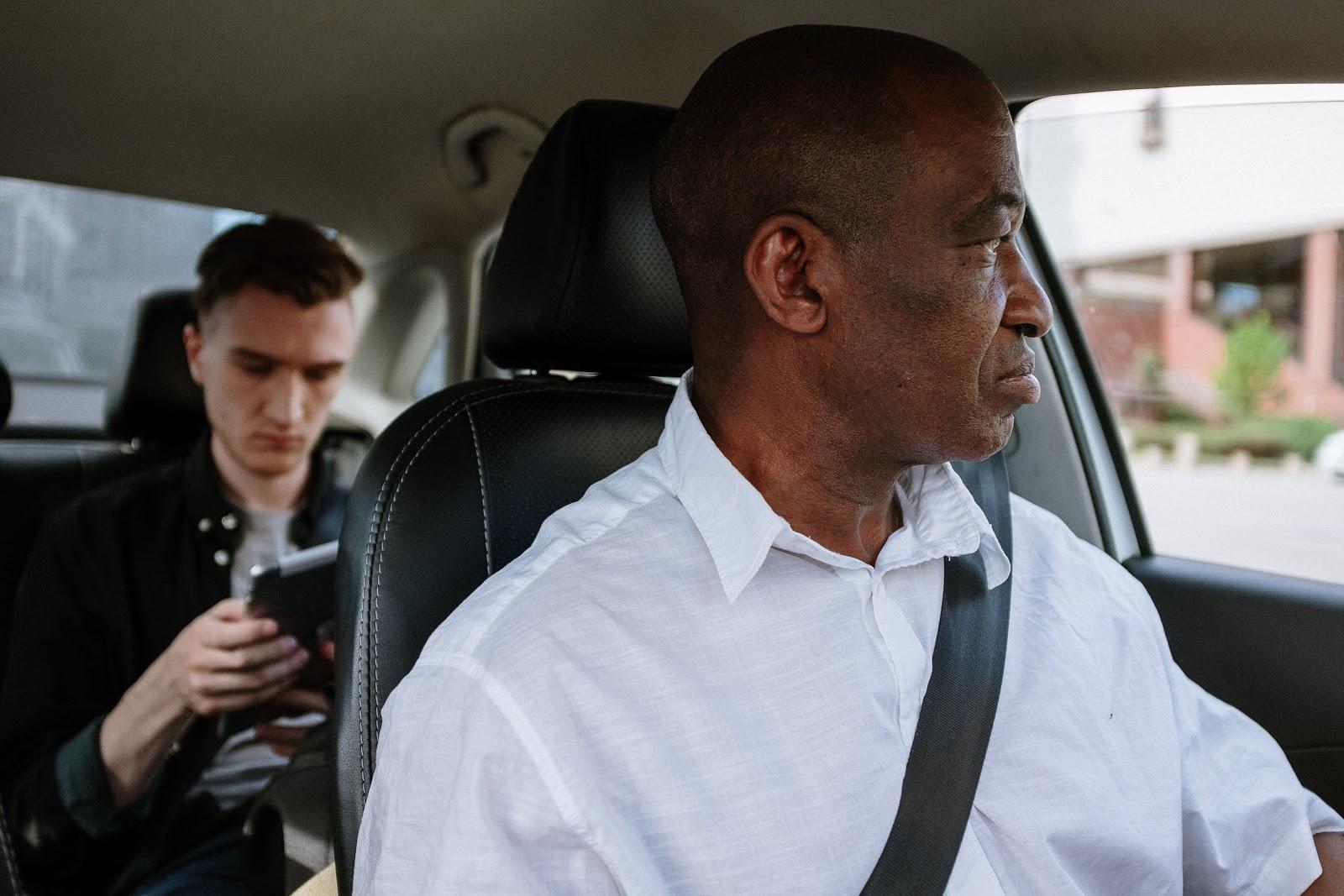 Motorista dirigindo e no banco de trás um homem verificando no celular quantas pessoas podem ir no Uber e 99