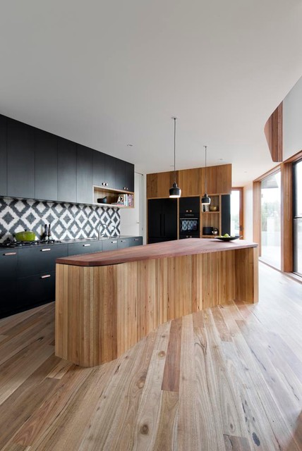 modern kitchen with rounded island, black cabinets, geometric backsplash and wood floor