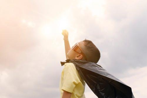 Boy Rising Up His Hand Wearing Black Cape