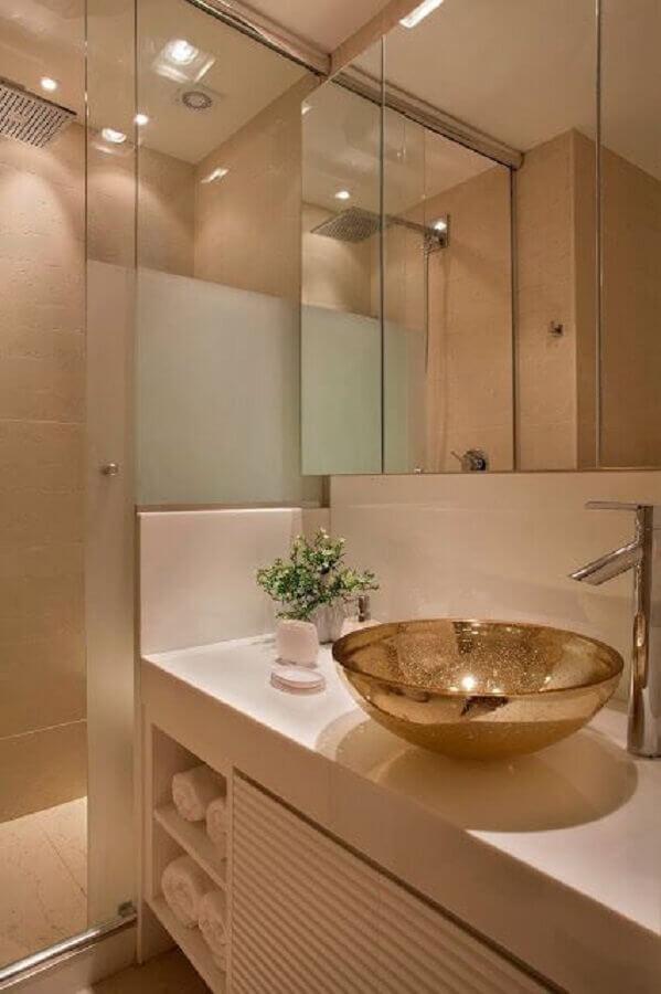 Vista lateral dos detalhes de um banheiro. Podemos identificar uma cuba redonda e dourada, um armário com espelhos e o box de vidro. Imagem para ilustrar a reforma de casas.