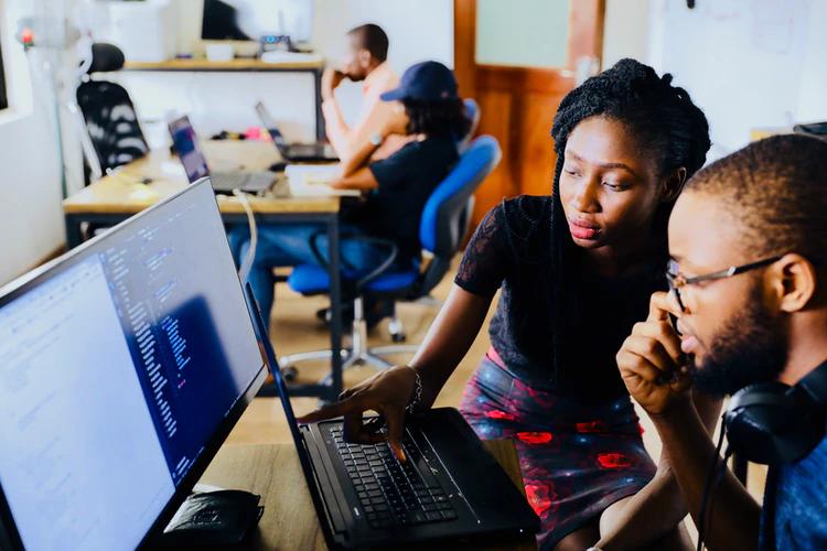 duas pessoas de frente apara o computador - pair programming