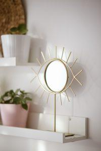 A small mirror in the shape of an eye. If you want to know how to use mirrors in interior design, try starting with smaller ones.