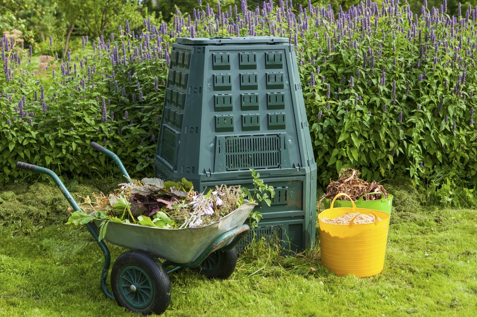 Image of a large compost bin in a garden with buckets of yard waste surrounding it.