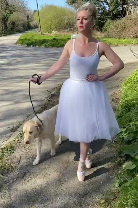Mujer vestida de bailarina pasea con perro