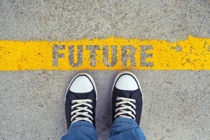"A person's feet standing by a yellow line with the word ""future"" reminding one to get to know your future self and stick to your budget."