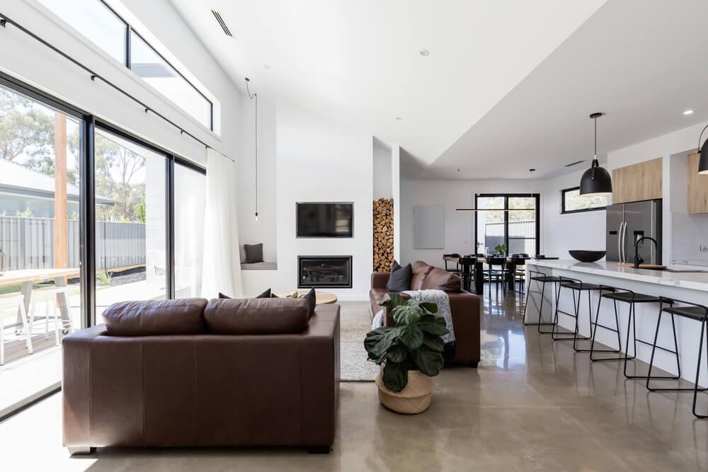 просторная гостиная с большим окном и бетонным полом