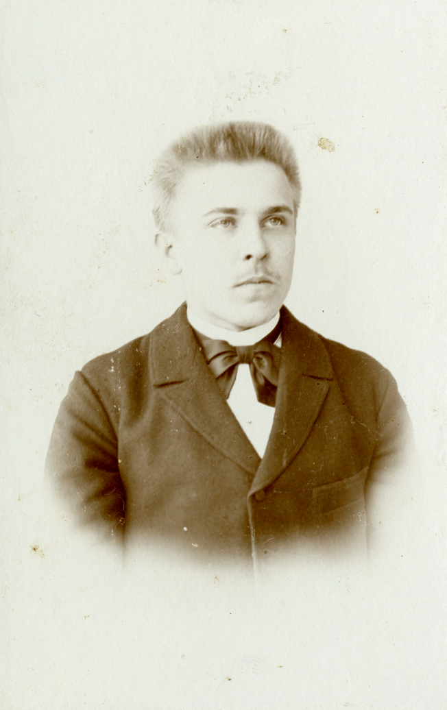 A vintage photo of a person wearing a suit and tieDescription automatically generated