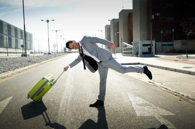 Joyful businessman playing with his suitcase  Shoe Colours For Suits