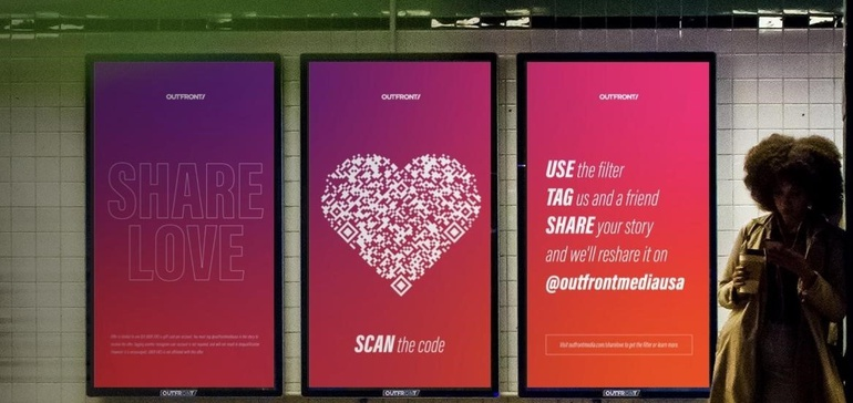 Valentine billboards in subway station, there is a QR code heart and it says 'Scan the code', on the other side it says 'Share Love' and 'Use the filter, tag us and a friend, share your story'