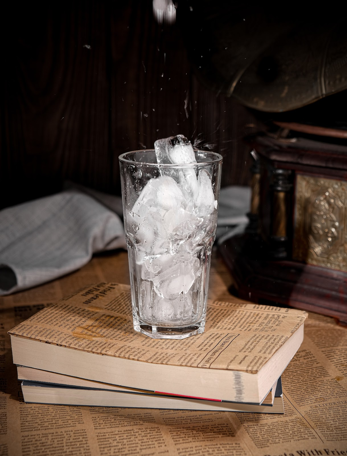A glass of melting ice rests upon a stack of books.