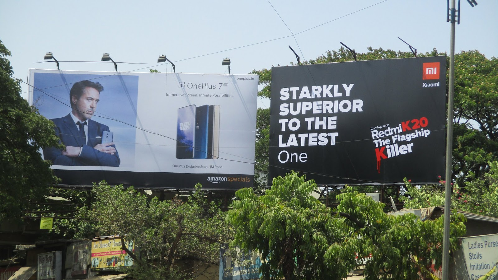 2 billboards next to each other about promoting new smartphones for OnePlus and Xiaomi