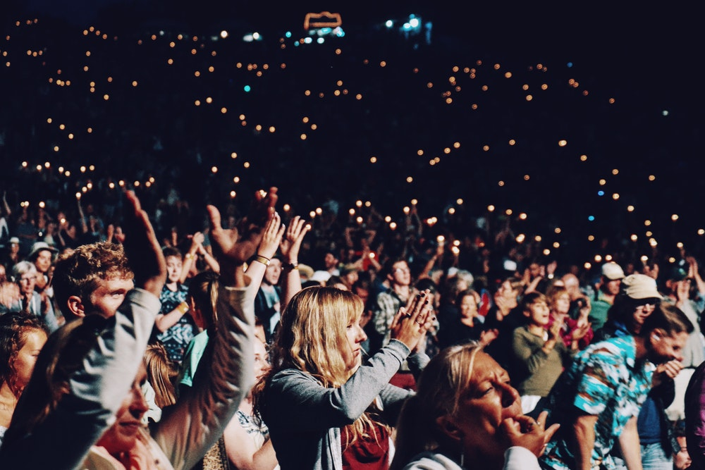A crowd of people cheering at an evening concert