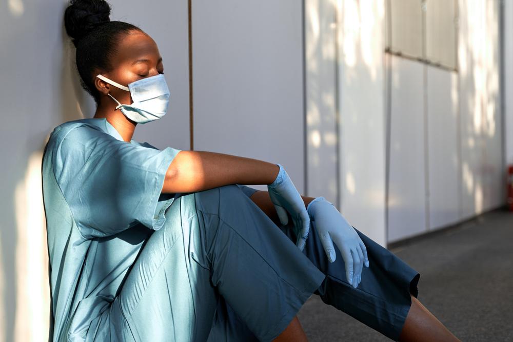 Médica sentada no chão escorada nos joelhos cansada