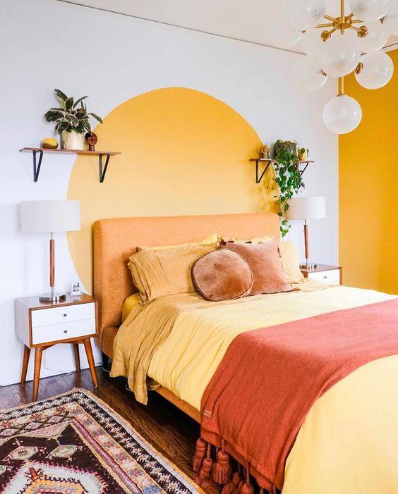 Quarto com cama de casal, parede branca com pintura de um grande circulo amarelo, piso de madeira e luminária pendente.