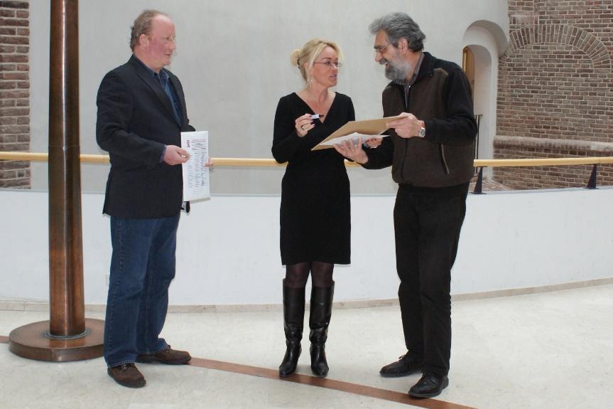 SP'ers Wim Musch (links) en Johan Oonk (rechts) bieden wethouder Schriks (midden) een petitie aan voor het behoud van betaalbaar openbaar vervoer in Zutphen