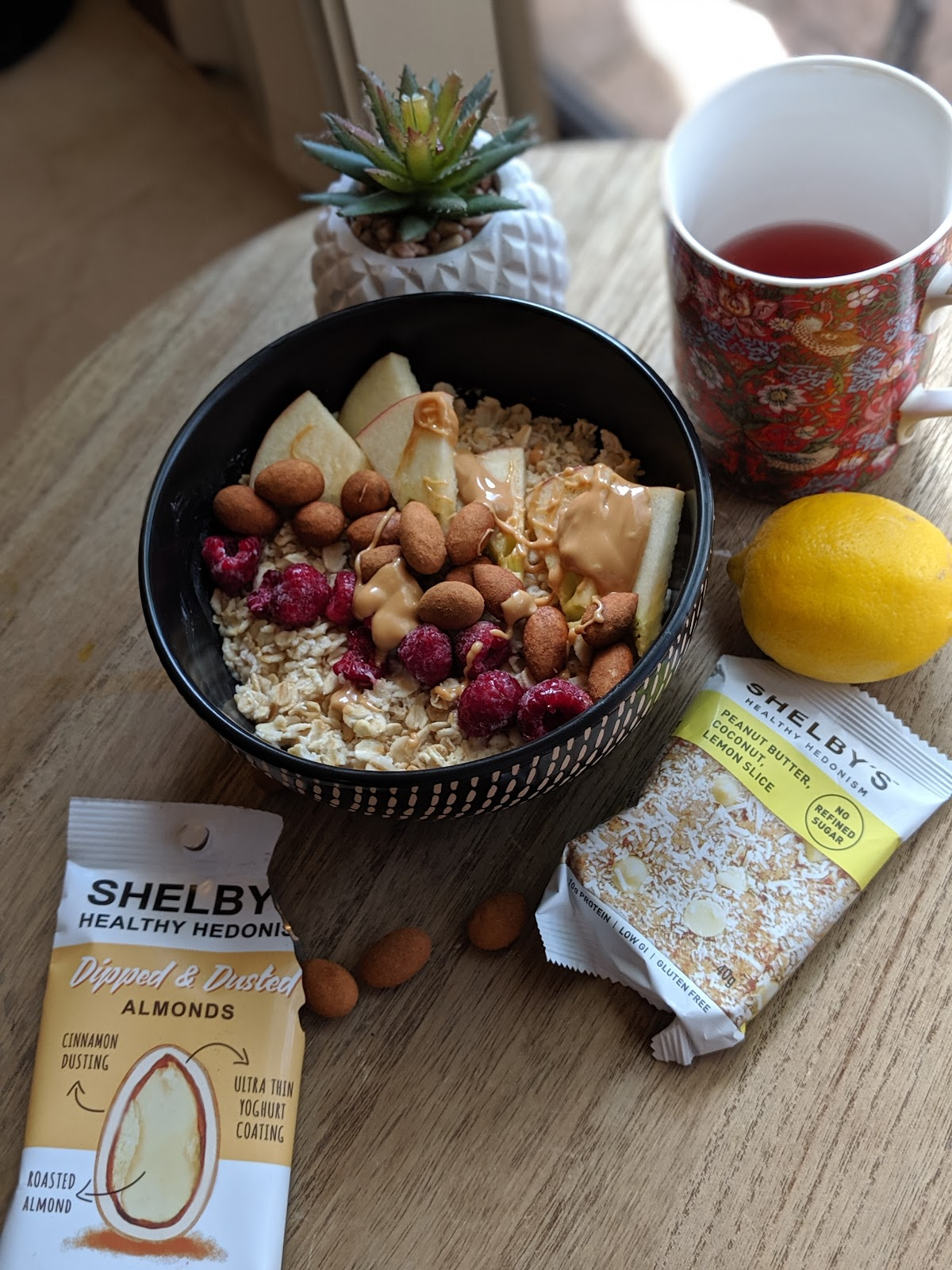 A bowl of oats topped with berries,apples and peanut butter, Shelby's Healthy Snacks dipped and dusted almonds. A cup of tea is beside the bowl.