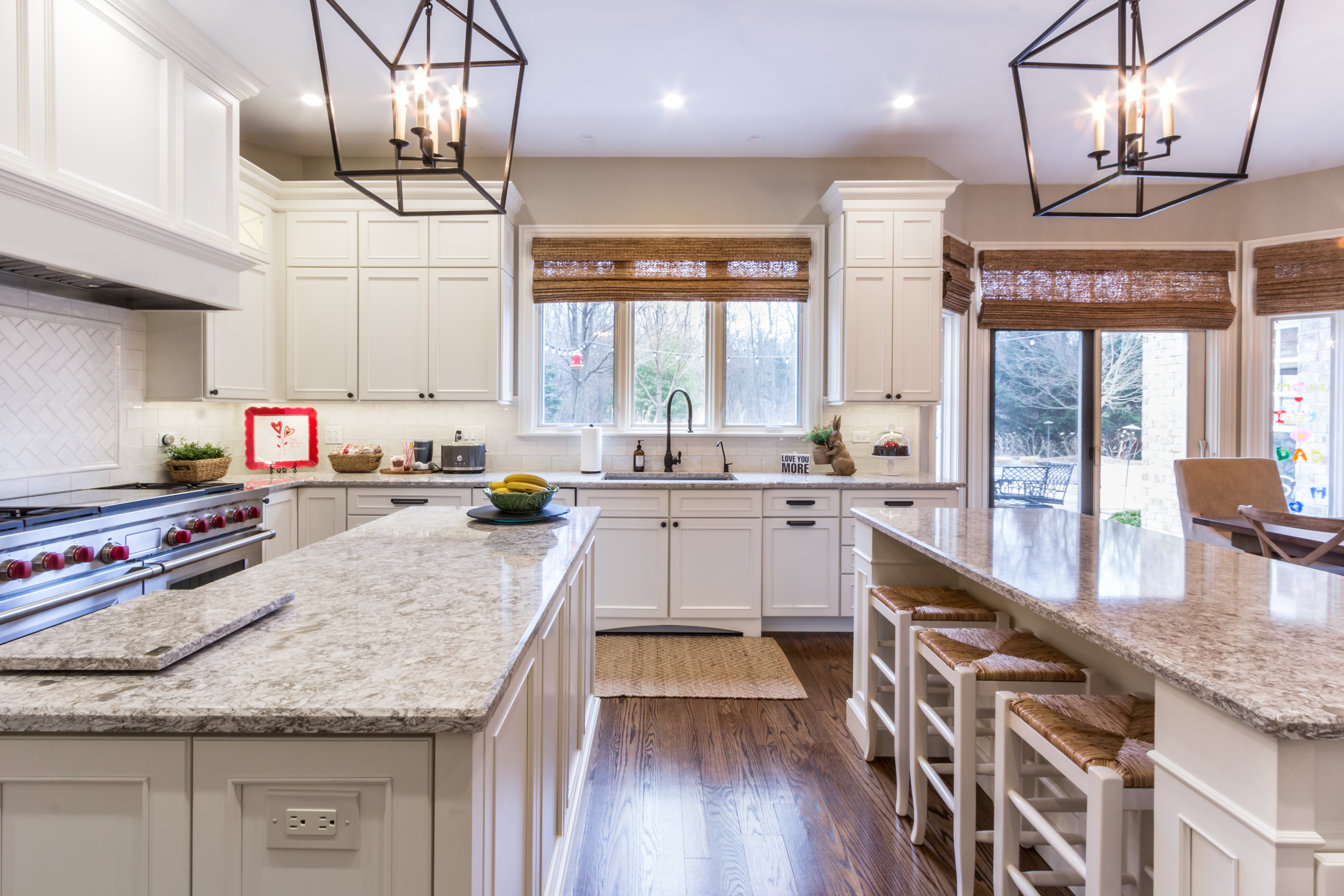 White kitchen with granite countertops, double island and metal framed pendant chandeliers.