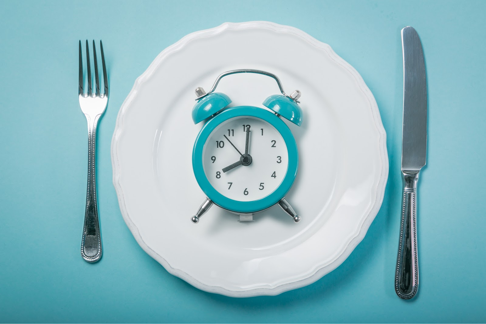 a clock on a plate with a knife and fork.