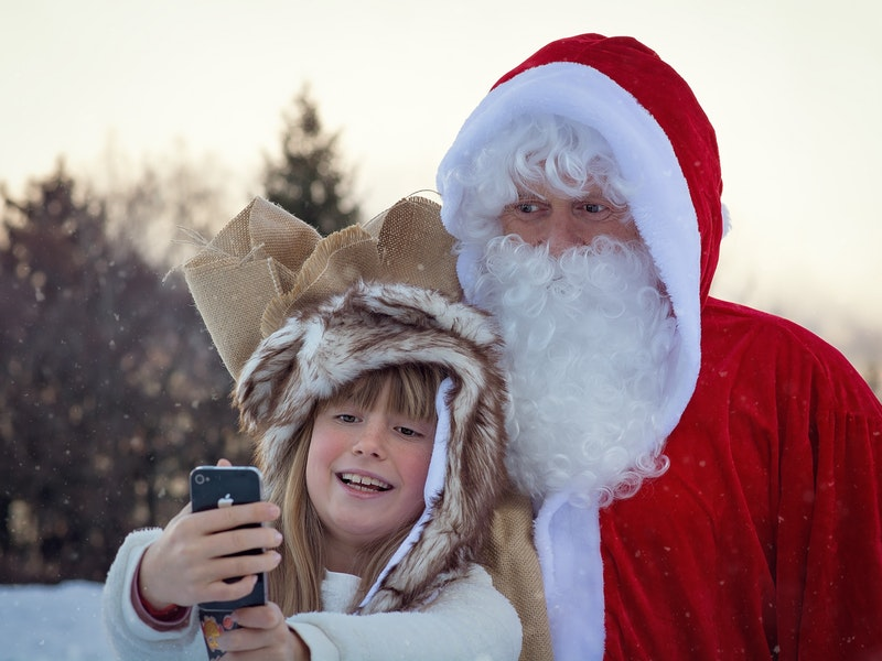 A young girl takes a selfie with Santa Claus