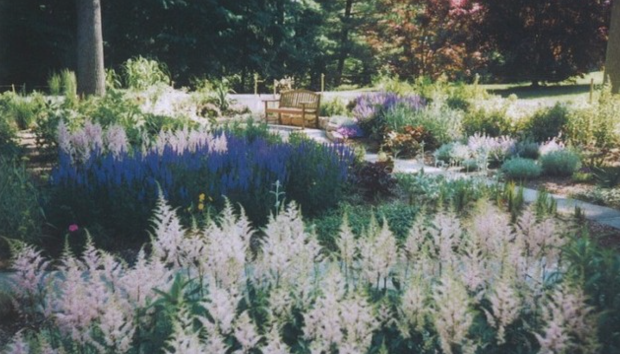A garden of every color with a pathway and seating area in Suburban Philadelphia