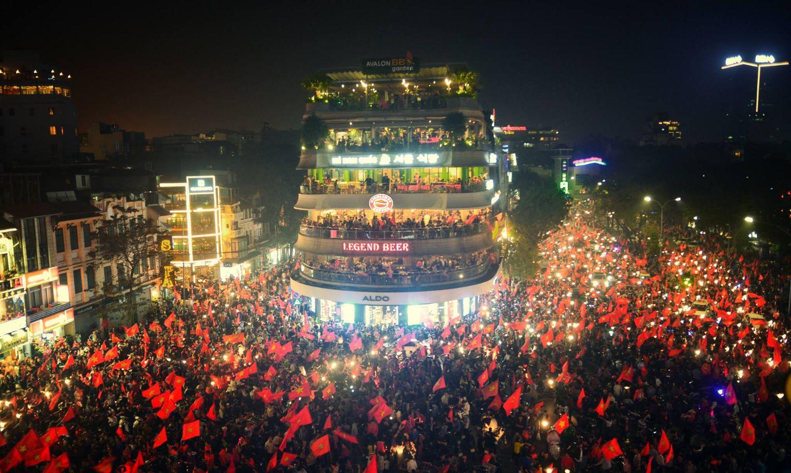 Vietnamese people cheer after Vietnamese football team won a match