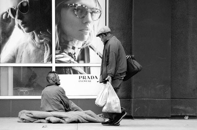 A homeless man in front of a luxury shop and a passerby approaching to him