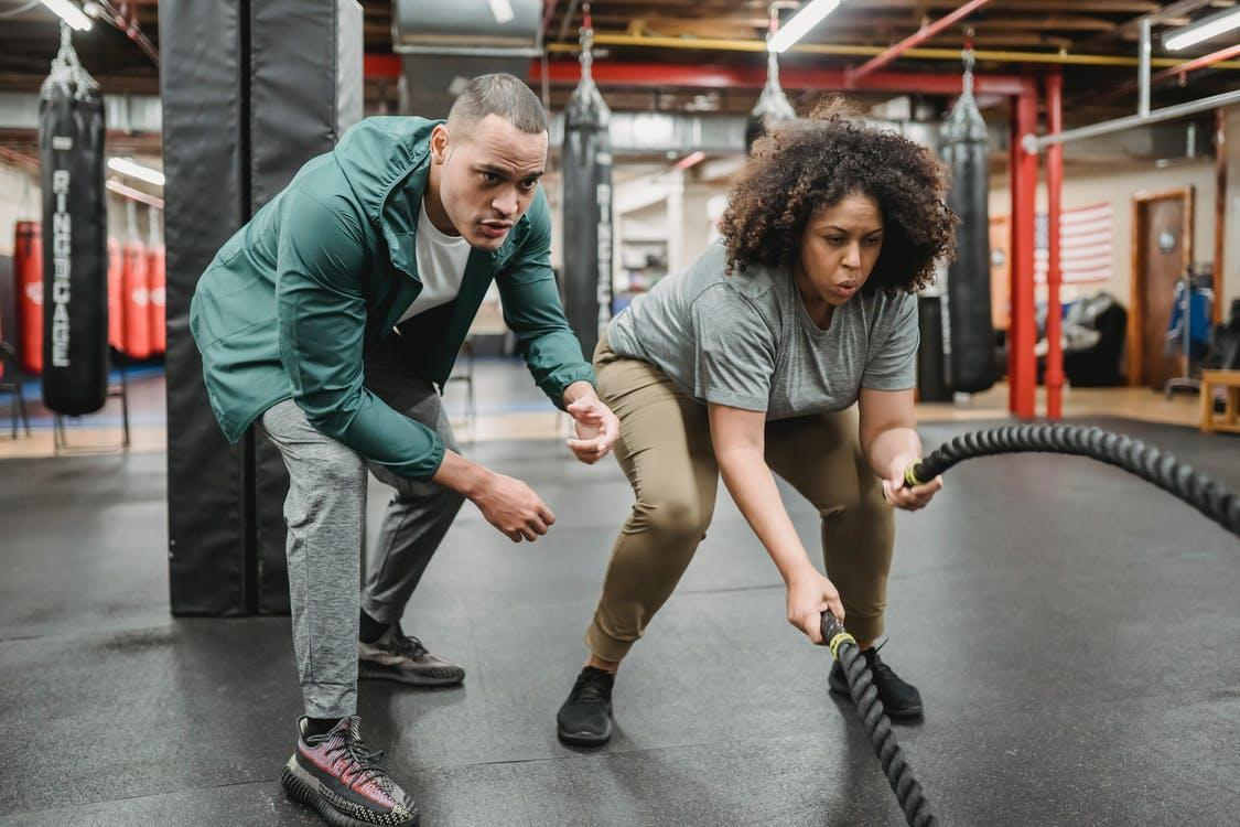 Determined black woman exercising with battle ropes near male coach