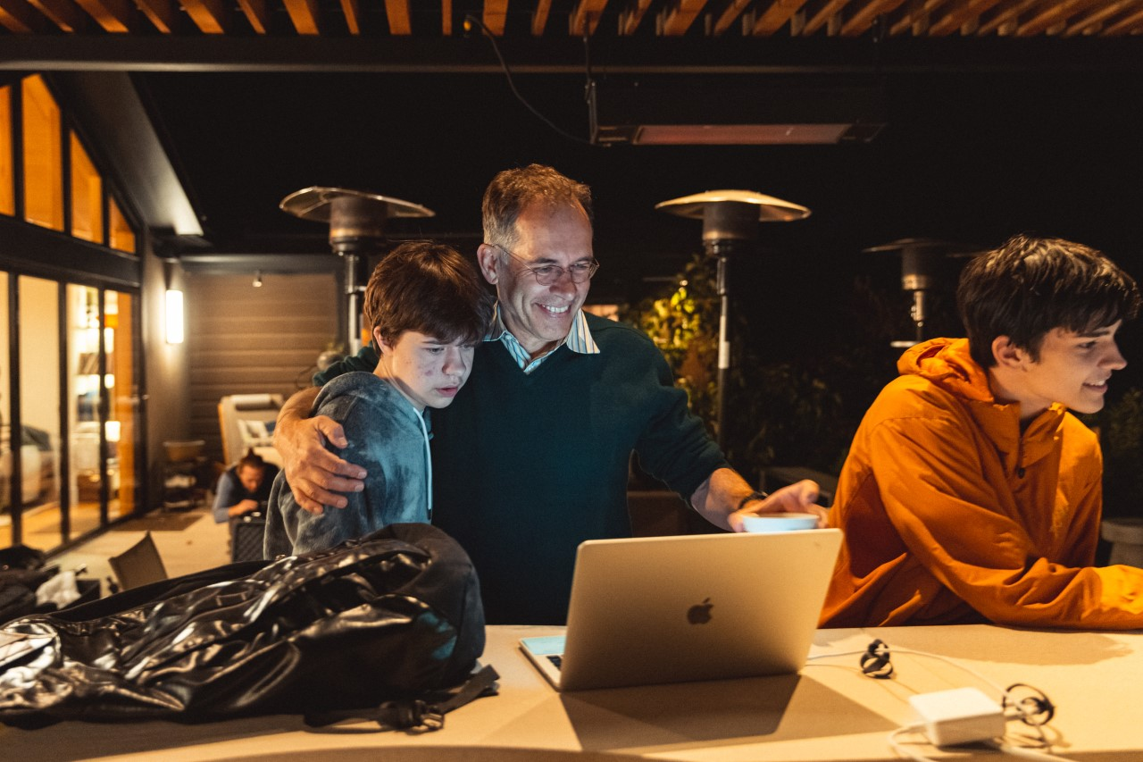 Stanford economics professor Imbens sits down with his two sons, smiling as he looks at his laptop.