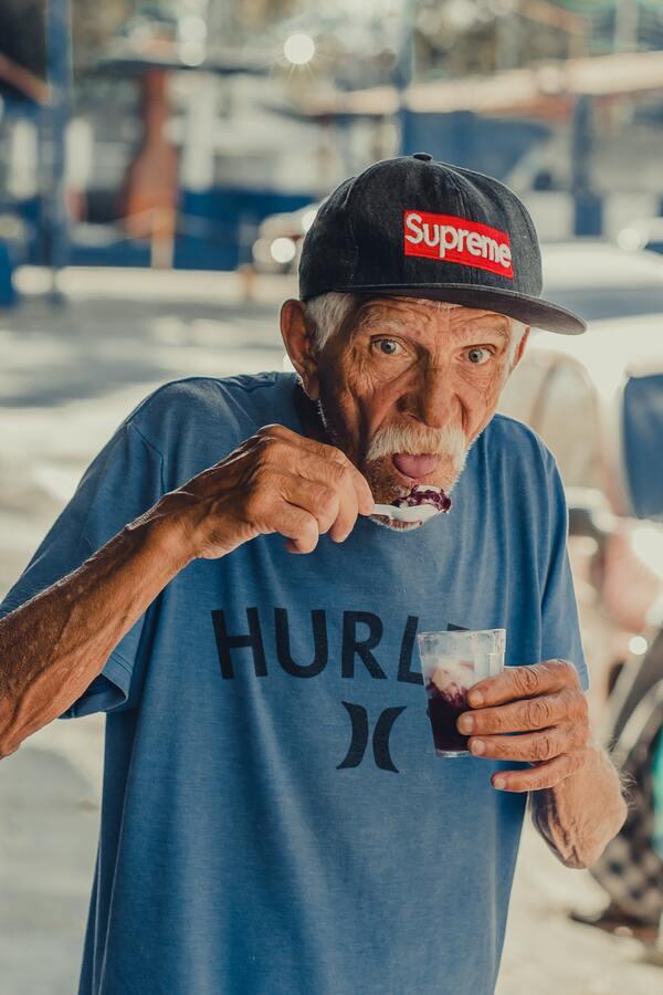 Avô tomando um açaí e sendo pego desprevinido pela foto
