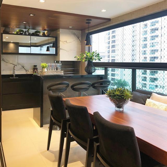 Área gourmet envidraçada com churrasqueira revestida de porcelanato marmorizado, bancada, armários e bancos pretos, mesa de madeira com cadeiras marrom e piso porcelanato branco.