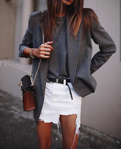 Woman wearing an oversized blazer along with a white ribbed mini skirt.